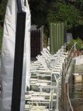 Linie von geschlossenen Strandstühlen und -regenschirmen bereit während der folgenden Sommersaison Toskana, Italien Lizenzfreies Stockfoto