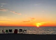 Linie von leeren Stühlen auf das Golf- von Mexikostrand während Floridas befestigt Sonnenuntergang Stockbilder