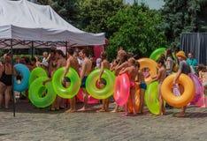 Linie von Leuten mit aufblasbarem Ring Wasserhügel ukraine Charkiw 10. Juli 2016 Stockfotografie