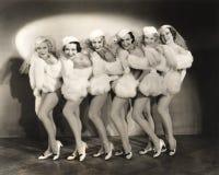 Linie von Revuetänzerinnen im weißen Pelz Stockbilder