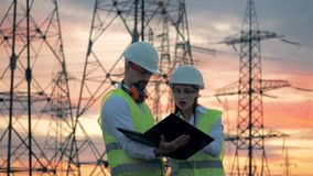 Linien der elektrischen Energieübertragung und zwei Techniker, die mit einem Laptop nahe ihnen arbeiten Mitarbeiter, die auf Plan stock footage