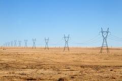 Linien der elektrischen Leistung unter einem blauen Himmel Lizenzfreies Stockfoto