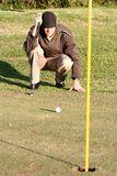 Lining up golf putt. A golfer on the green lining up his putt Royalty Free Stock Photo