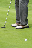 Lining up a putt. Male golfer lining up a putt on the golf green Royalty Free Stock Images