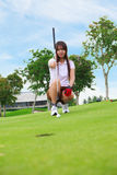 Lining up a putt on the green. Golfer young woman lining up a putt on the green Stock Photos