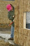 Lining Up the Wall to the Foundation. Woman construction worker checks the alignment of a plywood wall to the concrete foundation at a house construction site Royalty Free Stock Photos