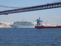 Liniowiec i czerwony freighter spotkanie pod mostem Kwiecie? 25 w Lisbon, Portugalia, Europa obraz stock