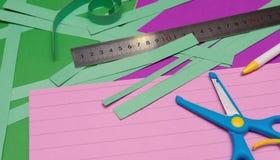 Linjal och sax och remmar för handsnittpapper arkivbild