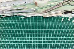 Linjal skärare, sax, band, blyertspenna, pappers- ark på bitande mor Arkivbilder