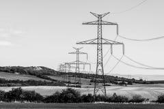 Linje av överföringstorn eller elektricitetspyloner, i det lantliga landskapet arkivbild