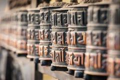 Linje av bönhjul in en by på den Annapurna strömkretsslingan Den buddistiska b?nen maler himalayas nepal askfat specificera royaltyfri foto