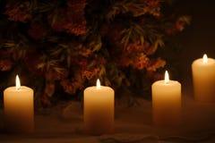 Linje av bränningstearinljus med torkade blommor royaltyfria foton
