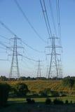 Linje av elektricitetsPylons över bygd Arkivfoto