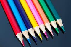 Linje av färgrika träblyertspennor på svart bakgrund royaltyfria bilder
