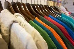 Linje av kläder på trähängare i lager försäljning Arkivfoto