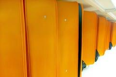 Linje av många orange bagage och resväskor på hyllatransportören arkivfoton