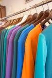 Linje av mång- kulör kläder på trähängare i lager försäljning Arkivbilder
