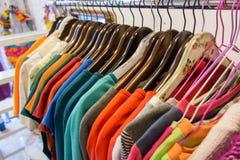 Linje av mång- kulör kläder på trähängare i lager försäljning Arkivfoton