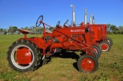 Linje av röda Farmall traktorer Arkivbild