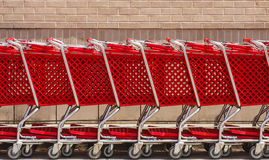 Linje av röda shoppingvagnar av Tegelsten Vägg Arkivbilder