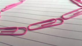 Linje av rosa paperclips royaltyfri fotografi