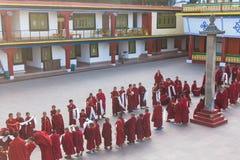 Linje av tibetana munkar framme av den Rumtek kloster för välkomnande på hög nivå munk nära Gangtok Sikkim Indien Arkivbild
