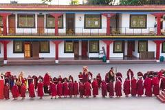 Linje av tibetana munkar framme av den Rumtek kloster för välkomnande på hög nivå munk nära Gangtok Sikkim Indien Royaltyfria Bilder