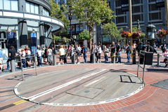 Linje av turister som väntar på en spårvagn på dess roterande stopp Arkivfoton