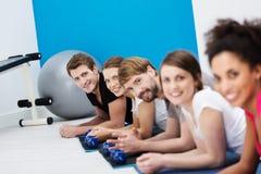 Linje av unga vänner som övar i idrottshallen Arkivfoto
