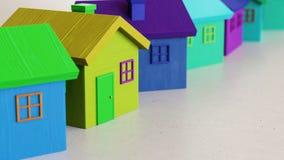 Linje av Vibrantly kulöra Toy Wooden Houses på enkla ljusa Grey Surface Royaltyfri Fotografi
