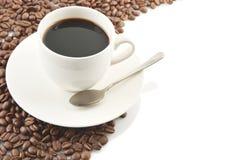 Linje som göras av kaffebönor med koppen kaffe arkivbild