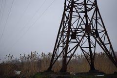 Linjer för lufthög-spänning överföring av elektrisk energi Över huvudet linjer lägger elektricitet ovanför jordning till och med  royaltyfri bild