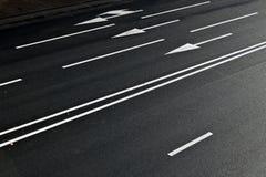 Linjer och pilar på asfaltvägen Arkivfoton