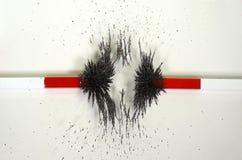 Linjerna av styrkor omkring två magneter med att motverka magnetfält royaltyfri bild