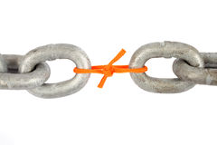Link. Two chains linked by a orange nylon rope isolated on a white background stock photos