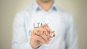 Link Building, Man writing on transparent screen. High quality stock photography