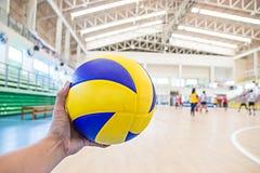 Linke Hand hält einen Volleyball Lizenzfreie Stockfotografie