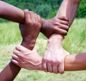 Linked hands. On a green background symbolizing teamwork and friendship stock photography
