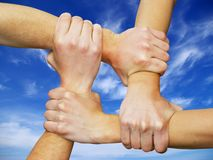 Linked hands. On a white background symbolizing teamwork and friendship stock photography