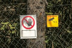 Linked wire fence with Keep out` and `Video surveillance` signs royalty free stock photos