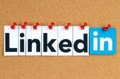 Linkedin logotecken som skrivs ut på papper, klipps och klämmas fast på korkanslagstavla Royaltyfri Foto