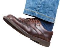Linkes Bein in den Jeans und im braunen Schuh unternimmt einen Schritt Stockfoto