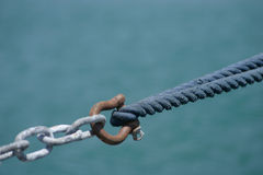 Linking. The rope of a yacht linked by a hook to a chain Stock Image