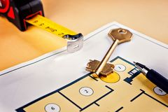 Linking new key on project plan of apartment house. Concept new residence house warming Buying Selling Real Estate Royalty Free Stock Photos