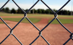 Through the Links. A view of a baseball diamond behind the fench with the chains links in focus Royalty Free Stock Images