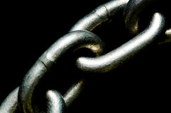 Links of a Chain. Links of a shiny silver chain on black background- importance of connection royalty free stock photography