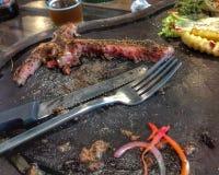 Links des Steaks des förmigen Knochens auf hölzerner Platte und Bier lizenzfreies stockbild