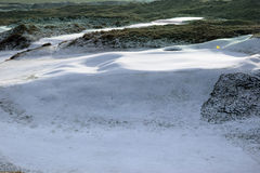Links golf course green with snow and yellow flag Stock Image