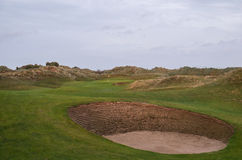 Links golf hole with bunkers and sand dunes. Golf hole on links course in sunset with large bunker and fairway in foreground and green and sand dunes in Stock Photo