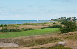 Links golf hole with ocean and holiday housings. Par 4 golf hole on links course with rolling fairway with shrubs, ocean, pier and holiday housing Royalty Free Stock Photography